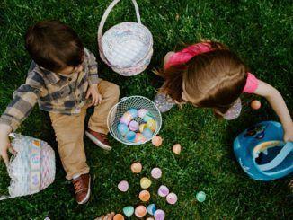 Dos niños juegan con huevos de Pascua en cestitas