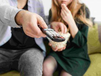 Dos personas utilizando un mando a distancia- series